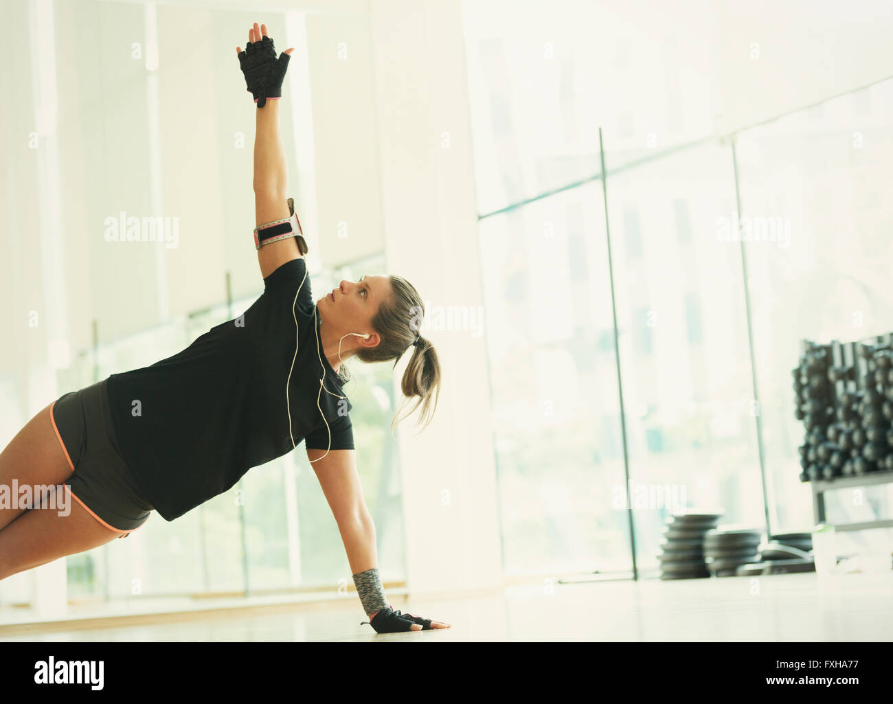 Woman balancing in side plank in gym studio - Stock Image