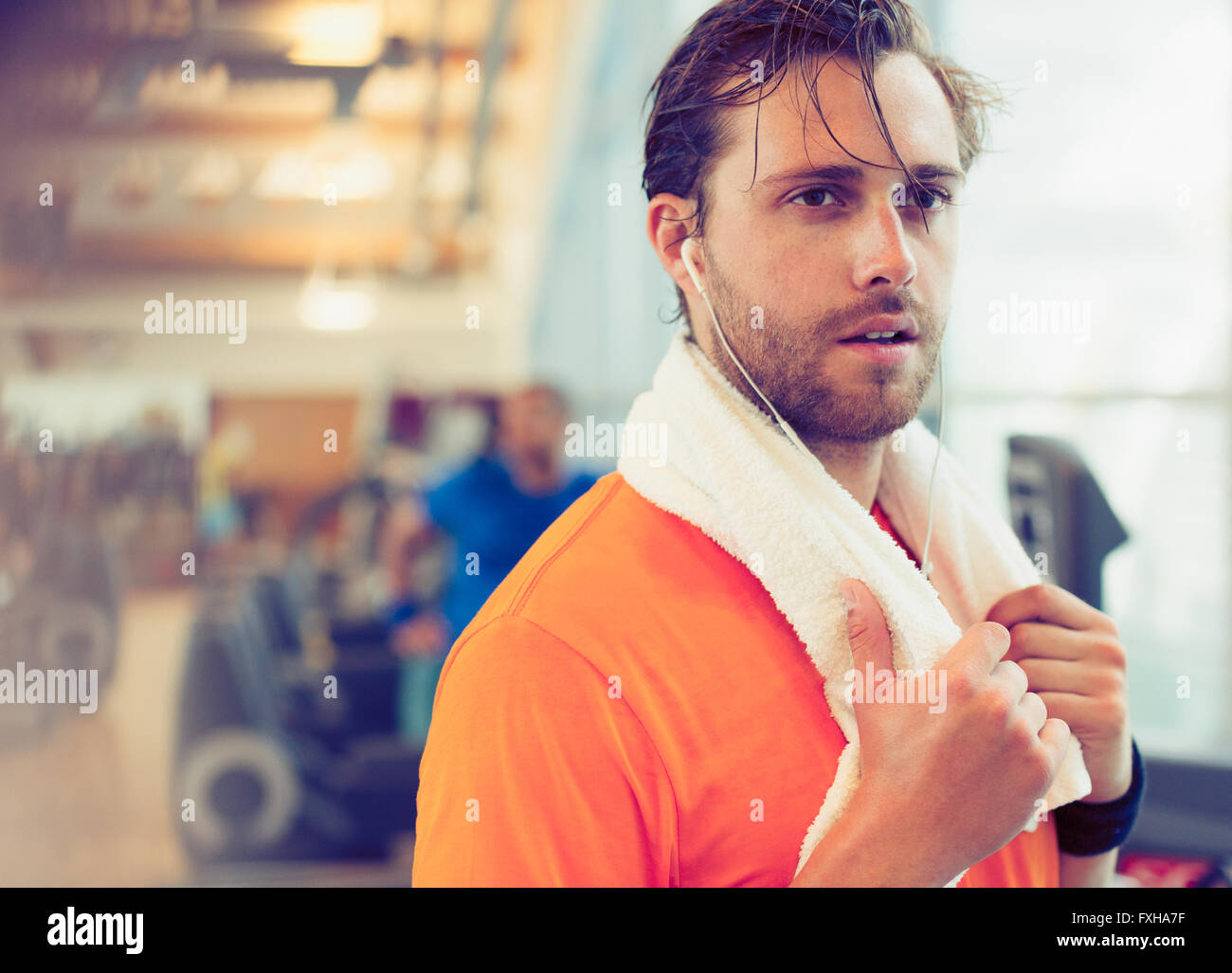 Sweating man with towel and headphones resting in gym - Stock Image