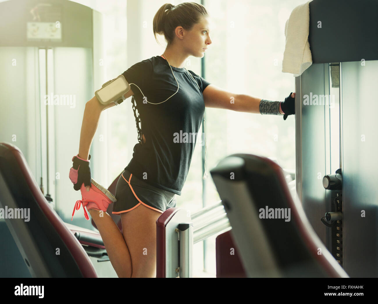 Focused woman stretching leg at exercise equipment in gym - Stock Image