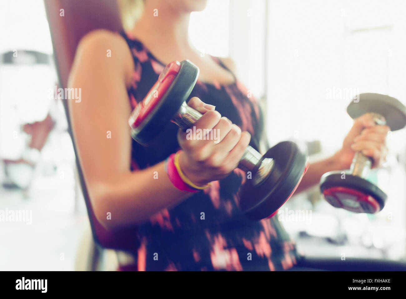 Blurred motion doing dumbbell biceps curls at gym - Stock Image