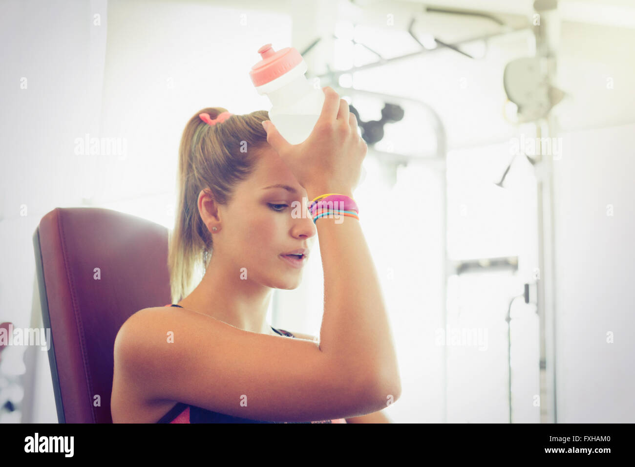 Tired woman cooling forehead with water bottle at gym - Stock Image