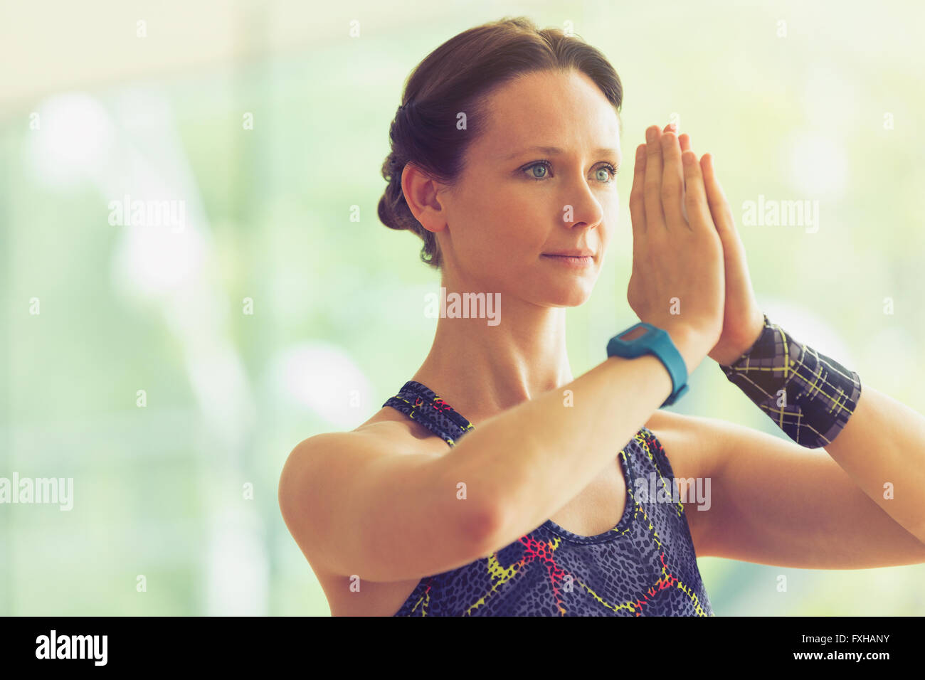 Calm woman with hands at prayer position in yoga class - Stock Image
