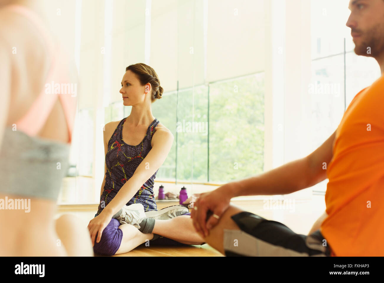 Fitness instructor leading class in twisting stretch - Stock Image