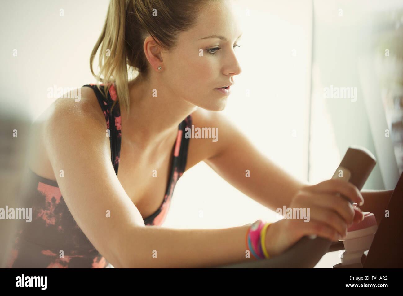 Focused woman using exercise bike at gym - Stock Image