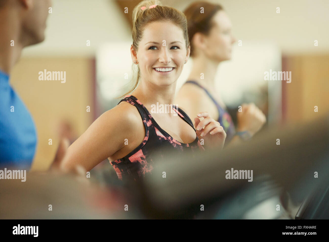 Smiling woman jogging on treadmill at gym Stock Photo