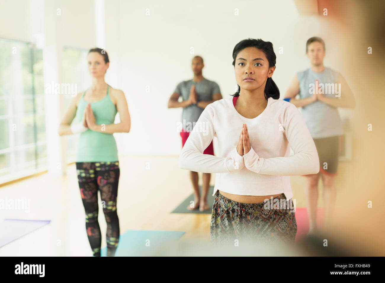 Focused woman with hands at prayer position in yoga class - Stock Image