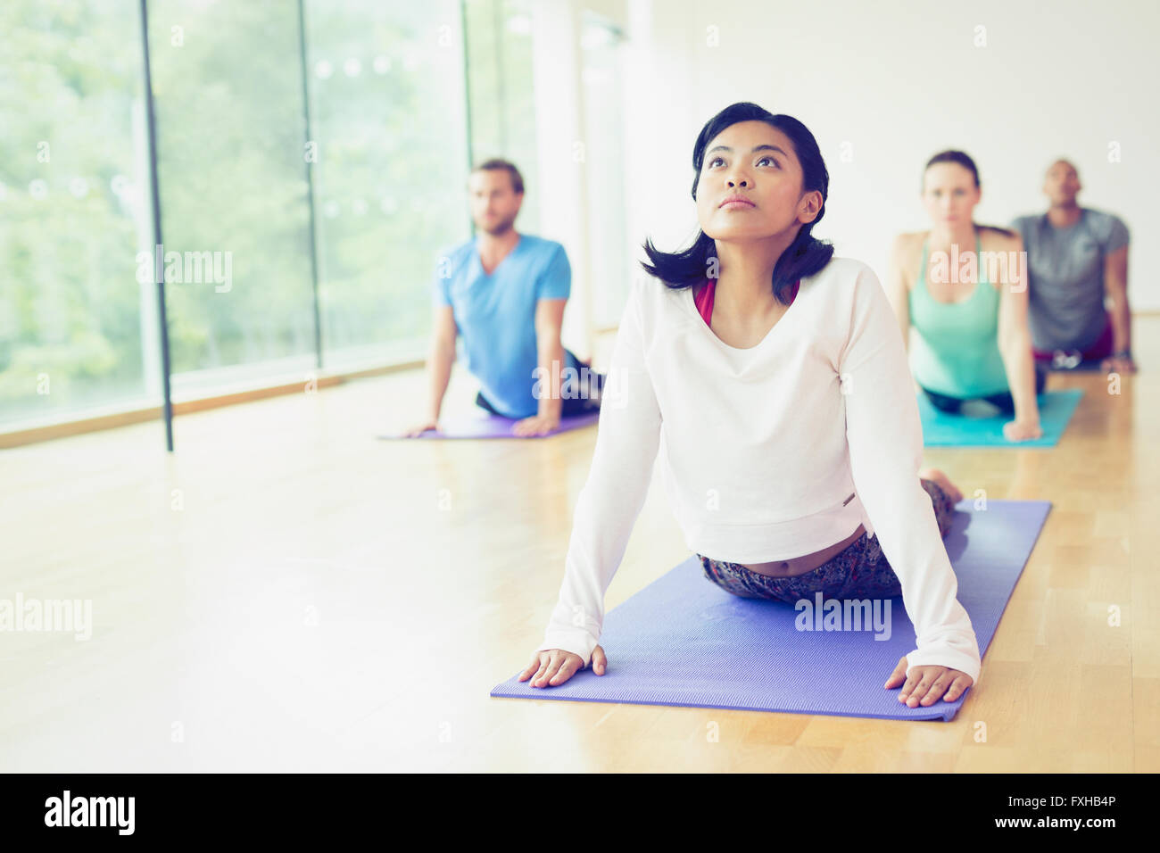 Woman in upward facing dog position in yoga class - Stock Image