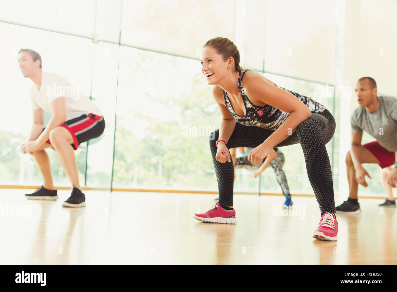 Smiling woman squatting in aerobics class - Stock Image