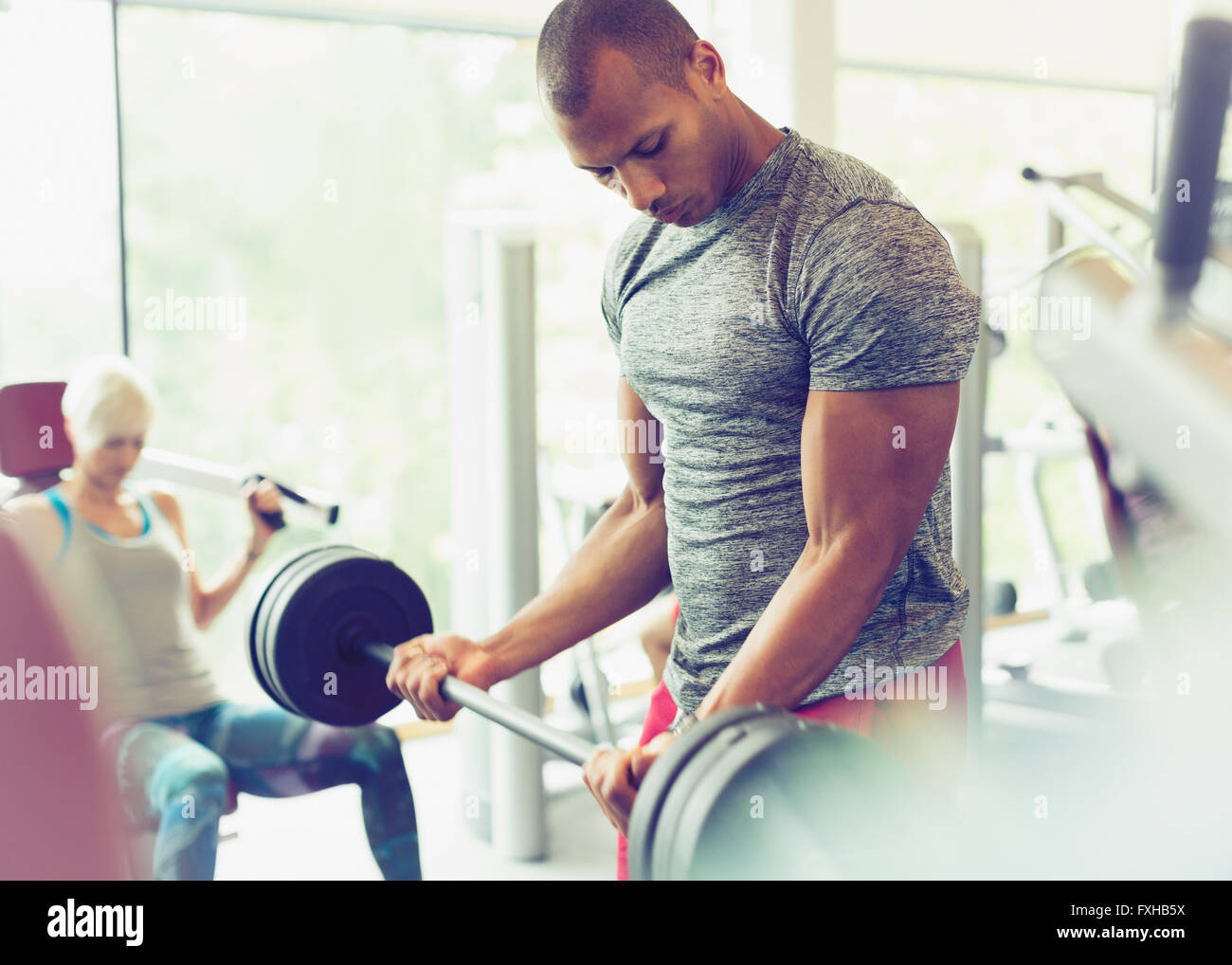Focused man doing barbell biceps curls at gym - Stock Image