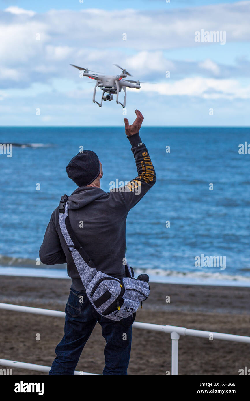 A man retrieves his remote-controlled zone standing next to the sea - Stock Image