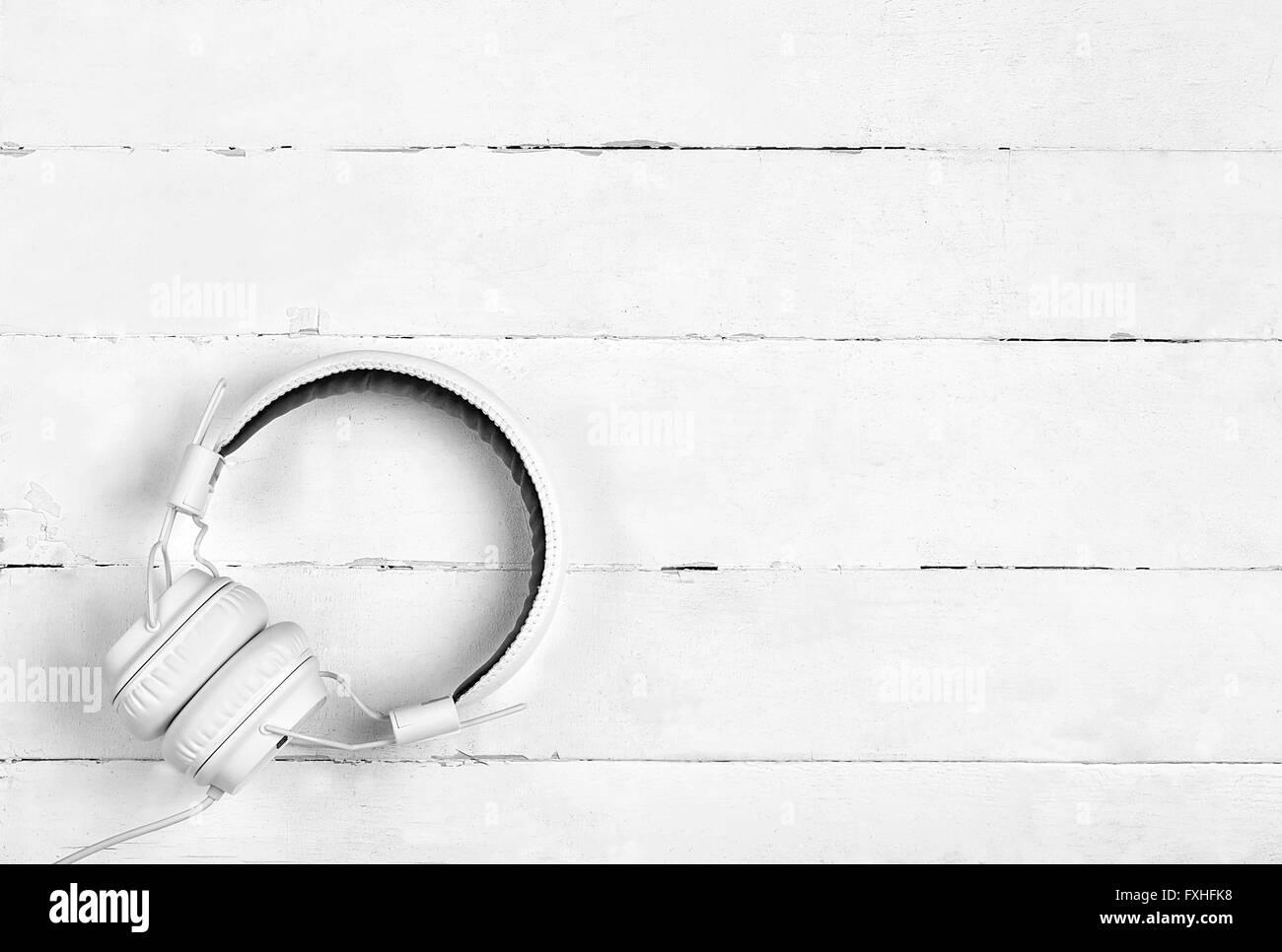 White headphones on white wooden table - Stock Image