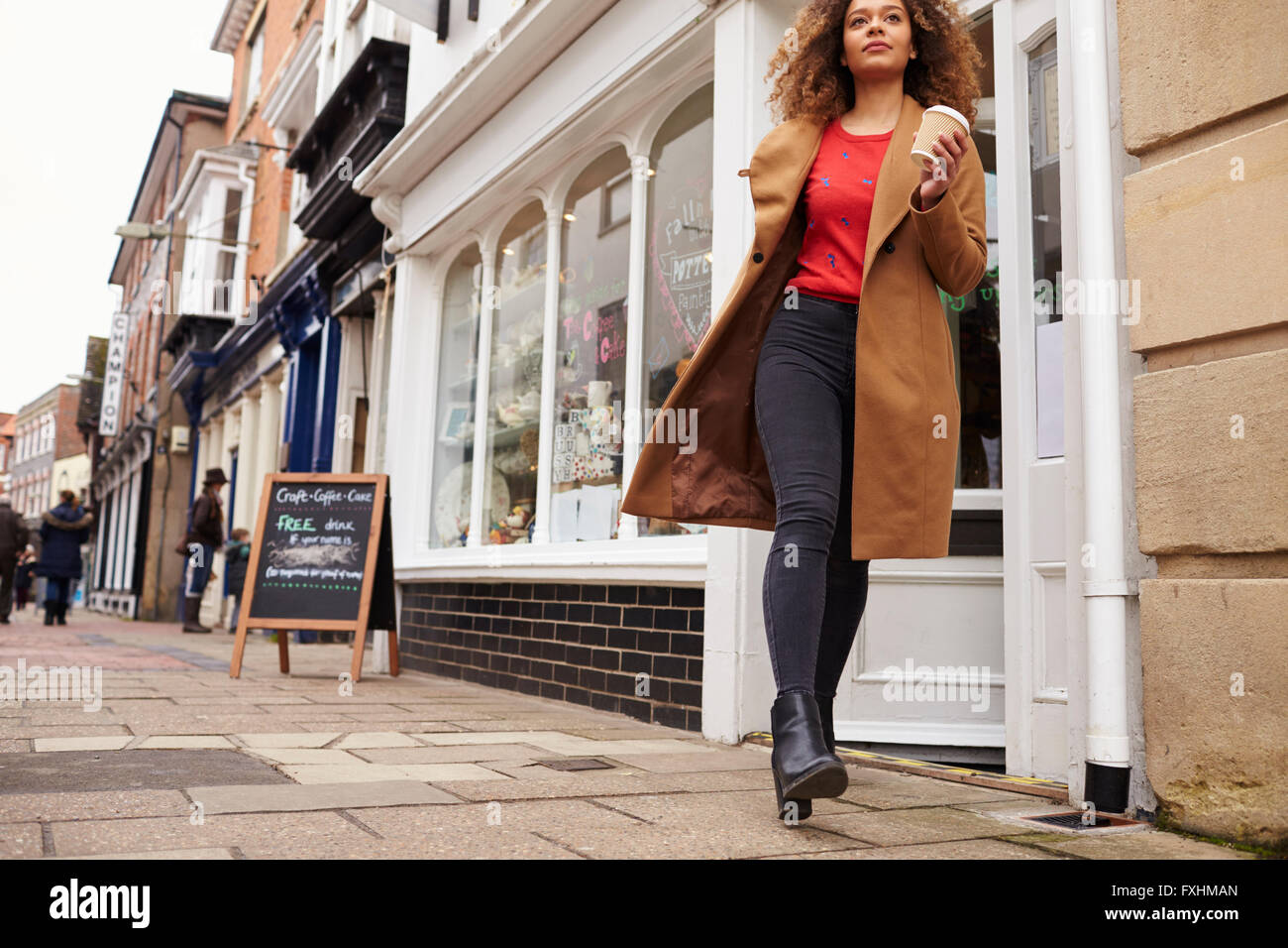 Female Customer Coming Out Of Cafe With Takeaway Coffee Stock Photo