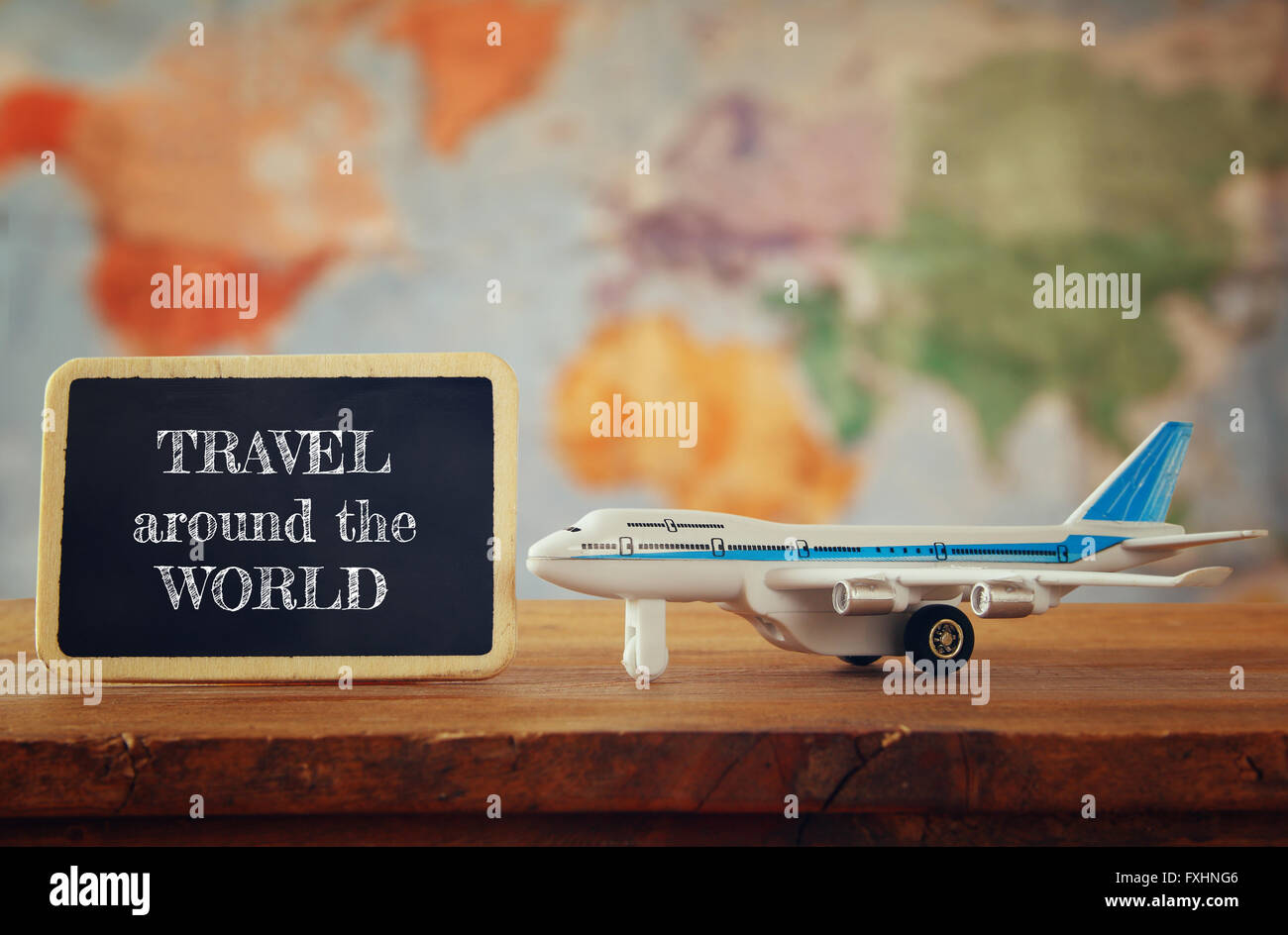 airplane toy next to blackboard. vintage filtered image. selective focus - Stock Image