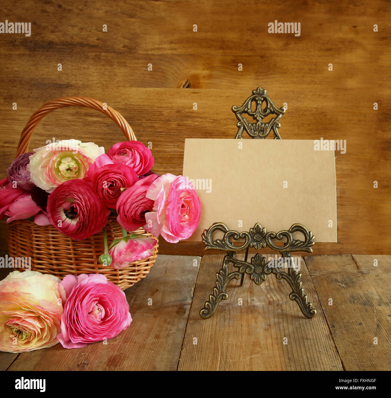 pink flowers in the basket next to empty card. mother's day concept. copy space. - Stock Image