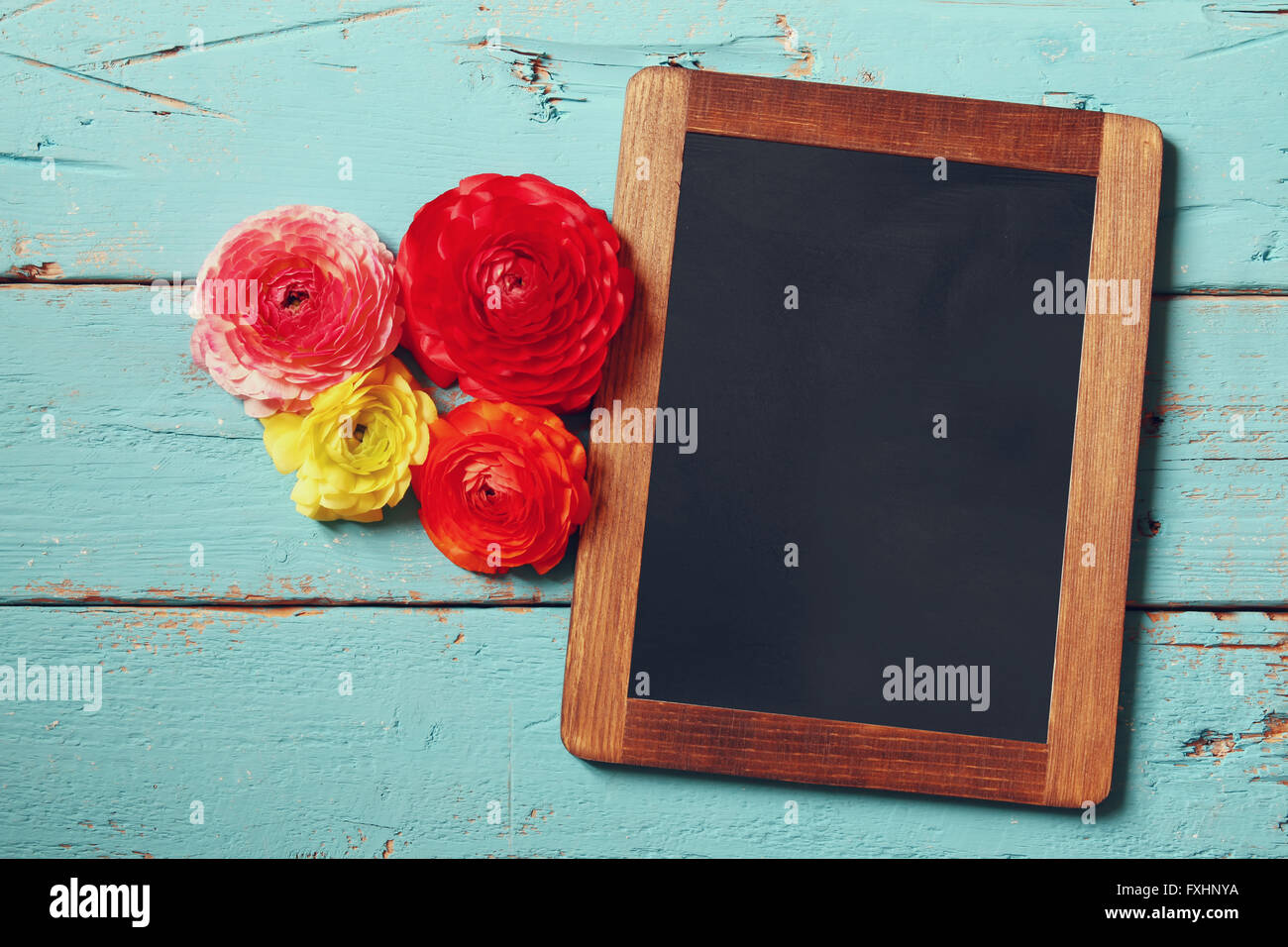flowers next to empty blackboard, on wooden table. copy space - Stock Image