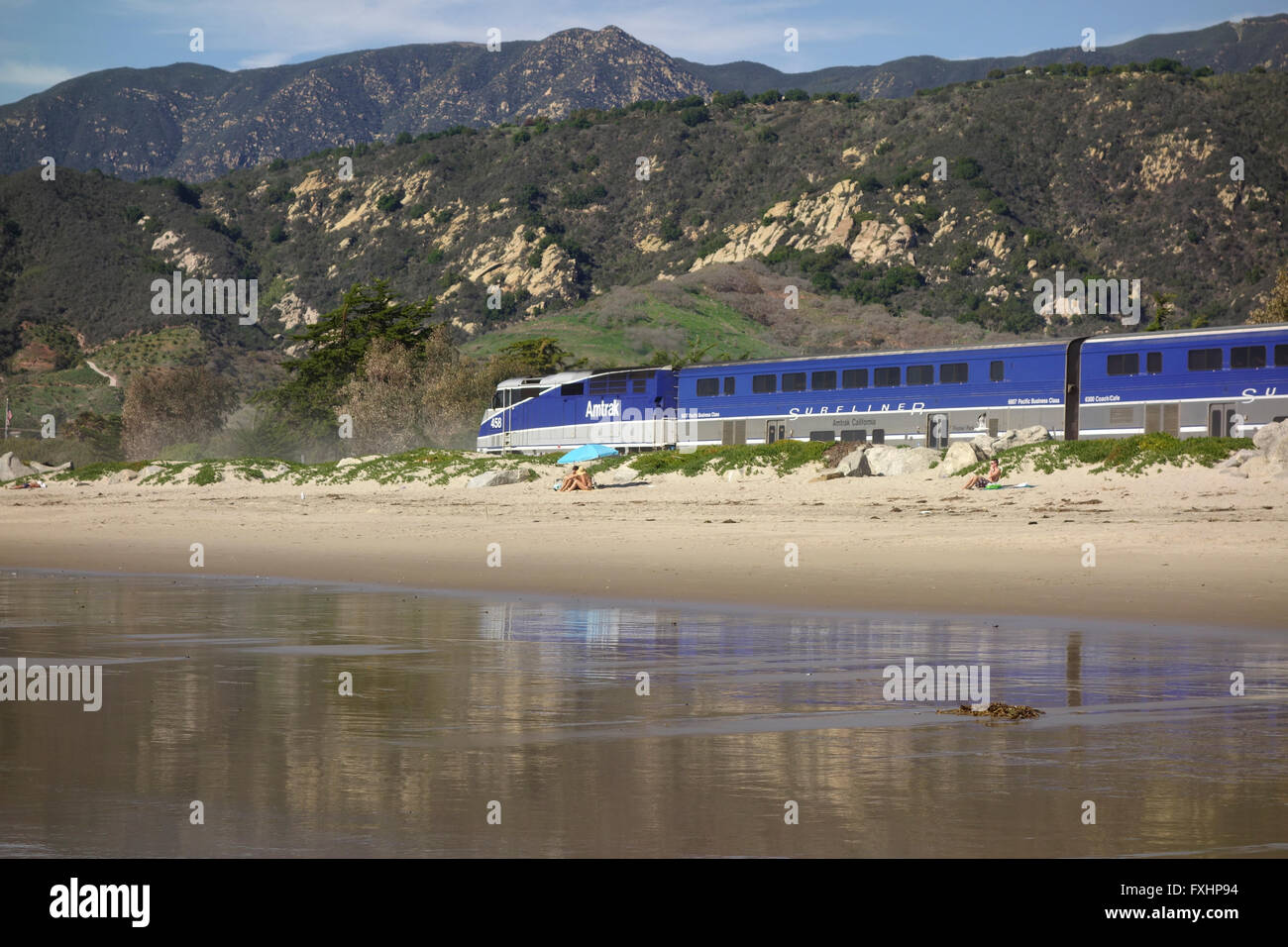 Amtrak Surfliner railroad locomotive on tracks along Pacific Ocean coast near Carpinteria in Southern California,United - Stock Image
