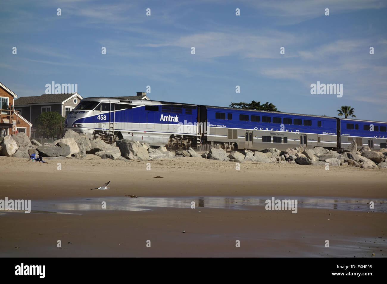 Amtrak Surfliner railroad locomotive on tracks along Pacific Ocean coast near Carpinteria in Southern California,United - Stock Image
