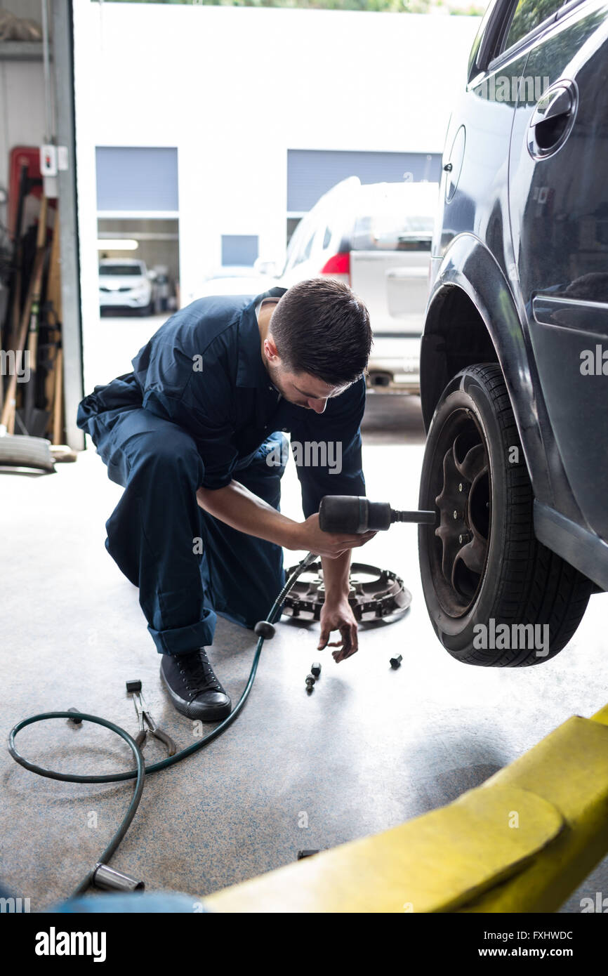Mechanic changing car wheel with pneumatic wrench - Stock Image
