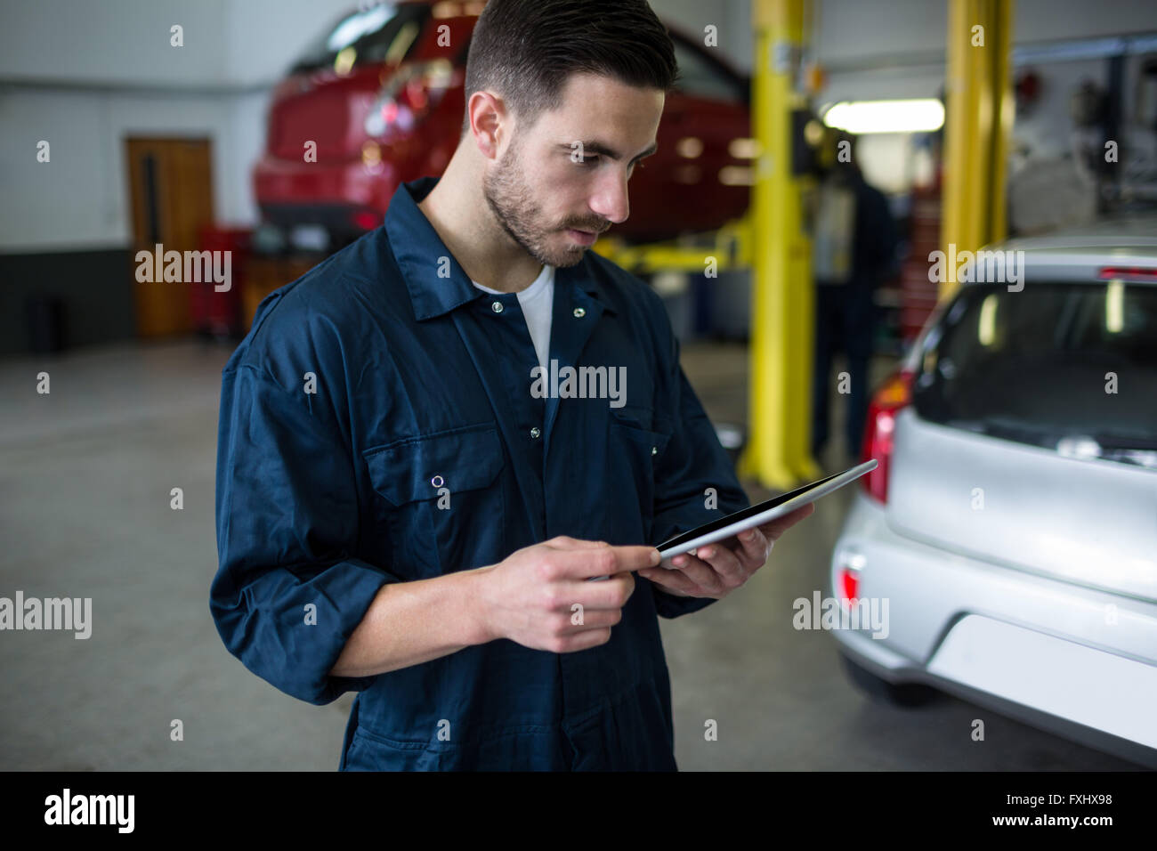 Mechanic using digital tablet - Stock Image