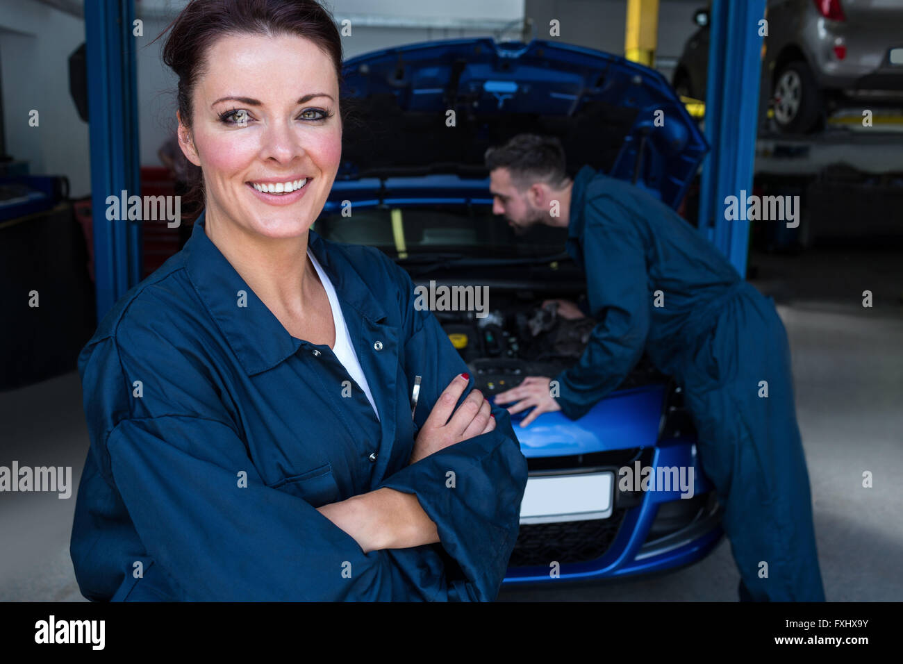 Female mechanic smiling at camera while her colleague examining car engine - Stock Image