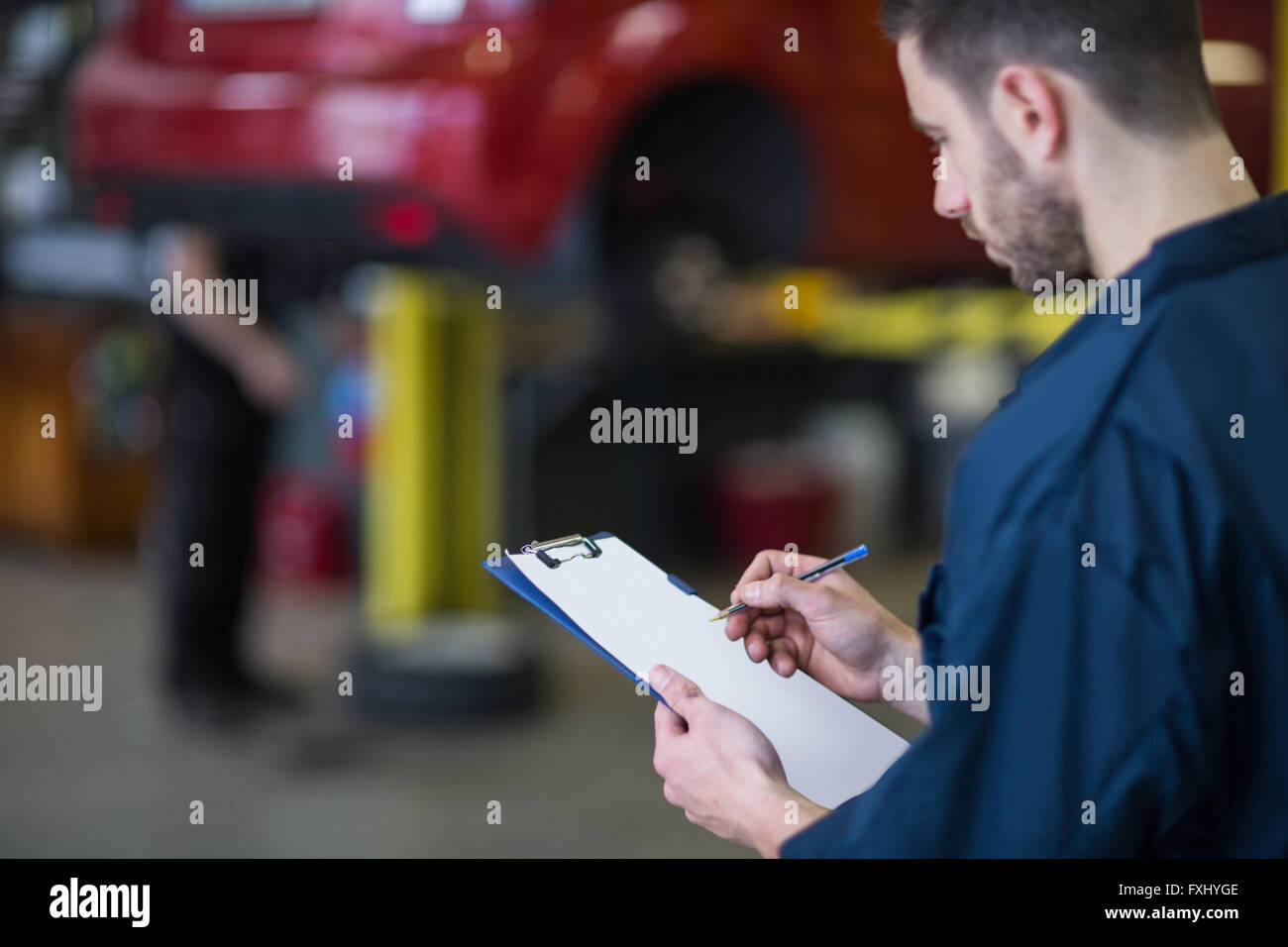 Mechanic preparing a check list - Stock Image