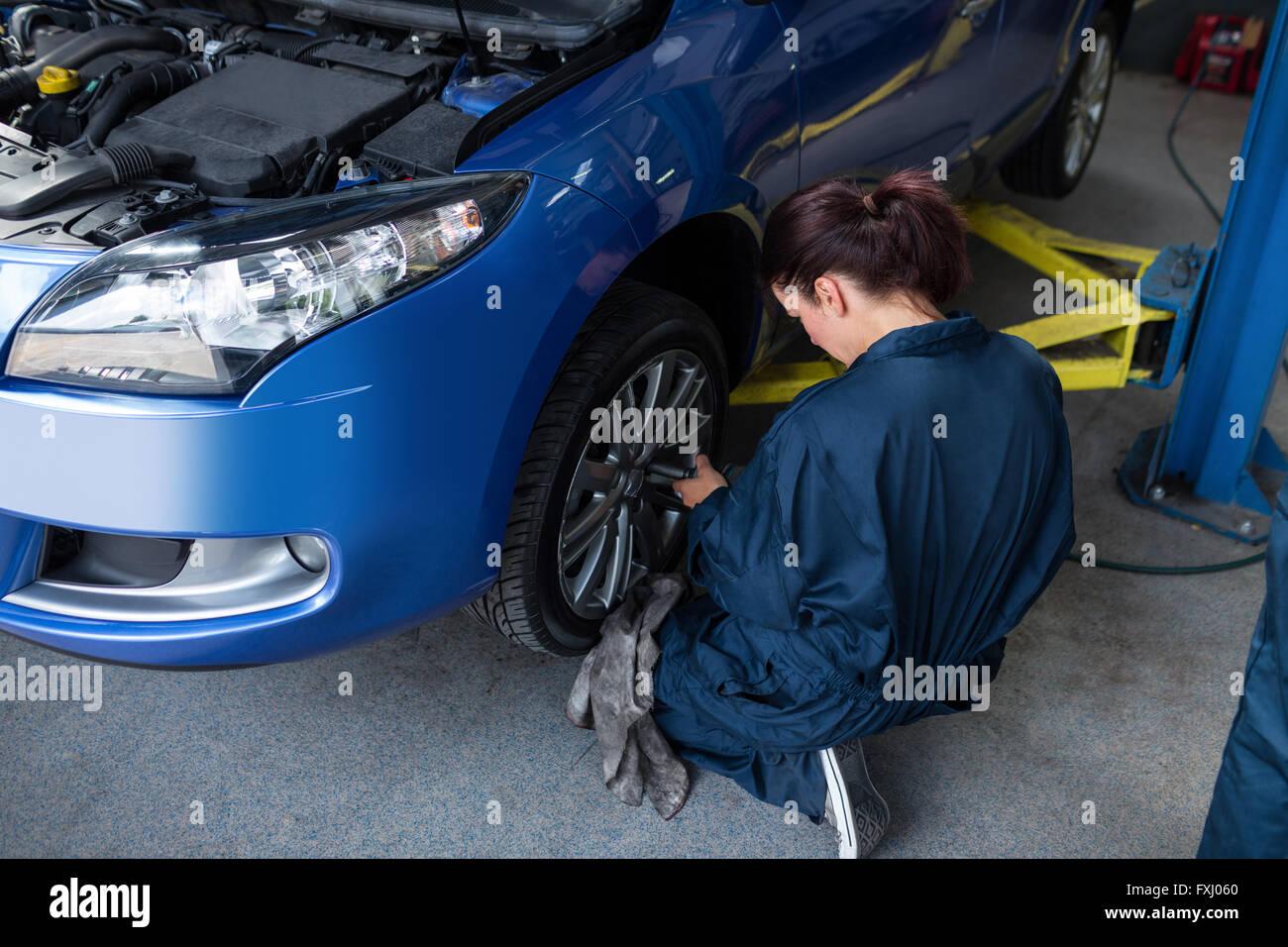 Female mechanic fixing a car wheel - Stock Image
