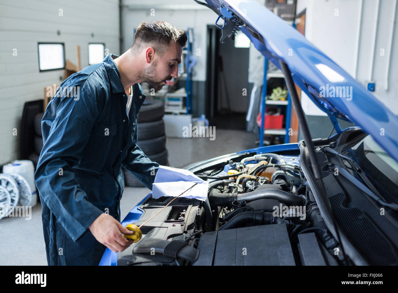 Mechanic checking the oil level in a car engine - Stock Image