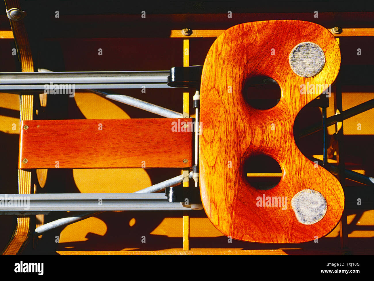 Close-up of the wooden sliding seat in a racing scull boat - Stock Image