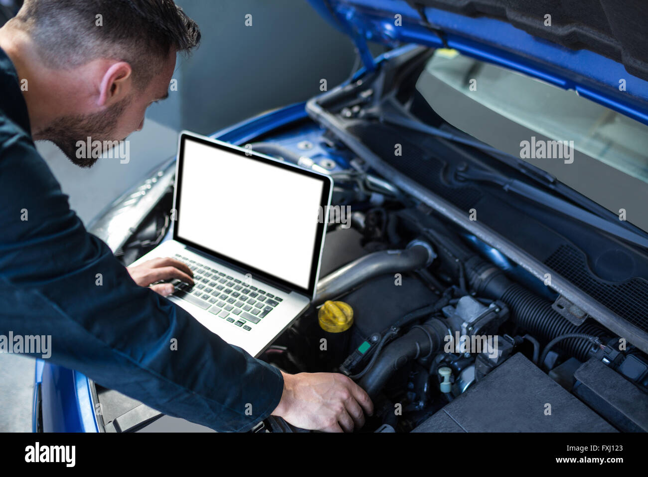 Mechanic examining car engine with help of laptop - Stock Image
