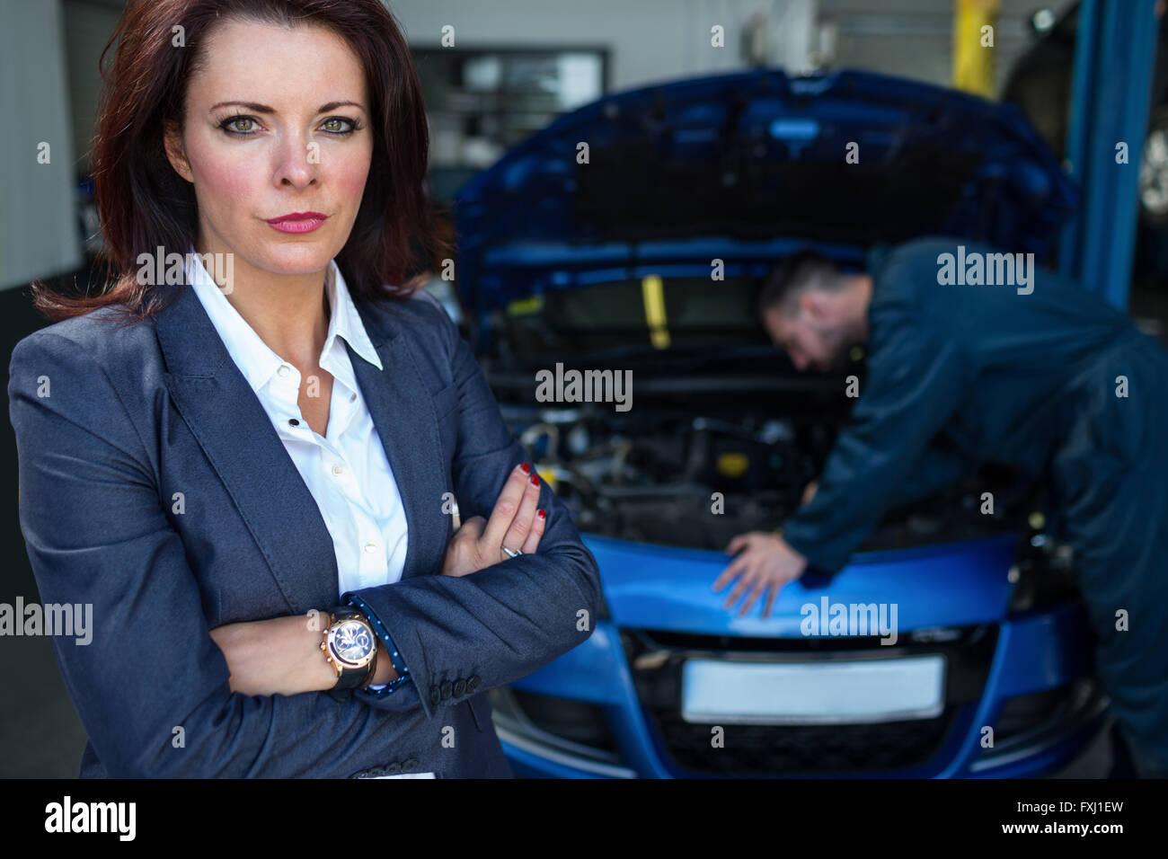 Customer looking at camera while mechanic examining car Stock Photo