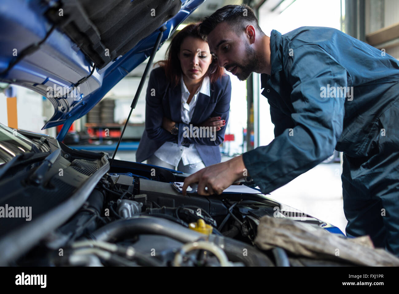 Mechanic showing customer the problem with car - Stock Image