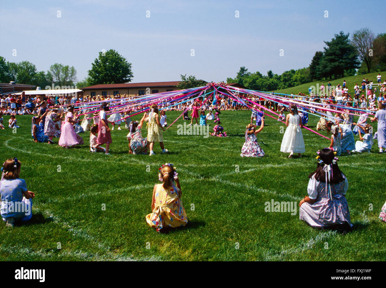 Elementary school children dancing around the May Pole; May Day - Stock Image