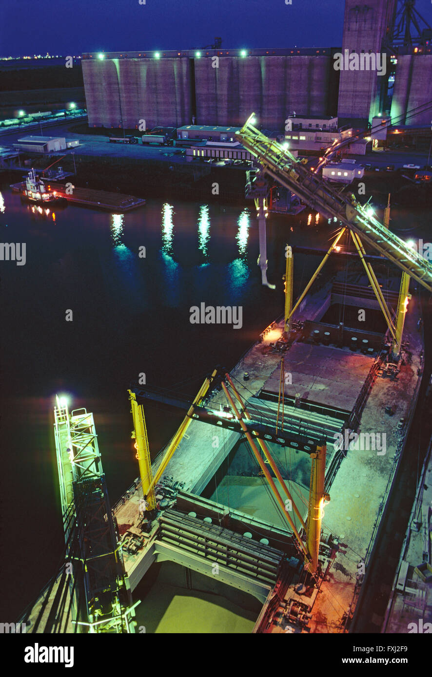 Night view of loading grain from silos onto a freighter ship in the Houston Texas Ship Channel; Texas; USA - Stock Image