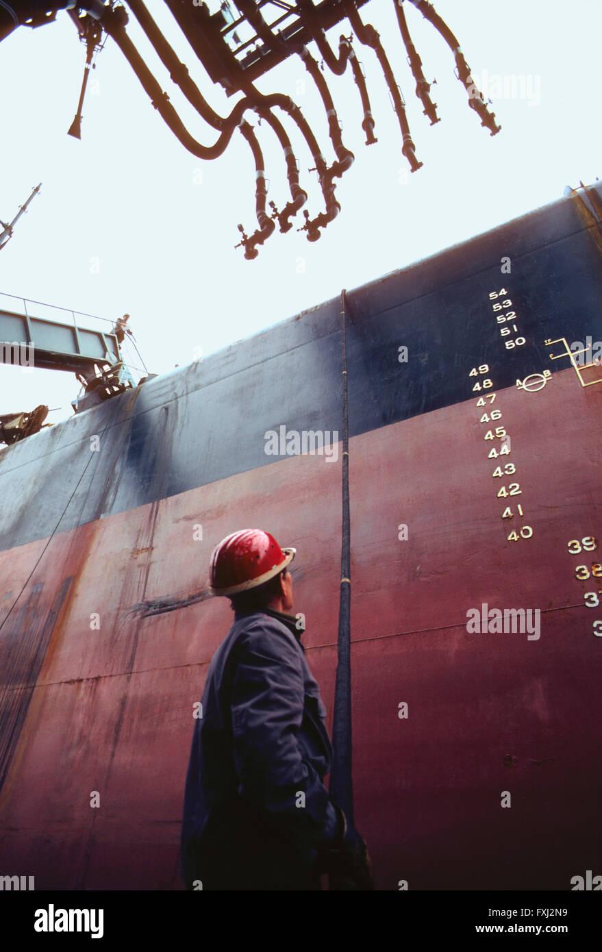 Dock worker preparing oil tanker for unloading; Hamburg; Germany - Stock Image