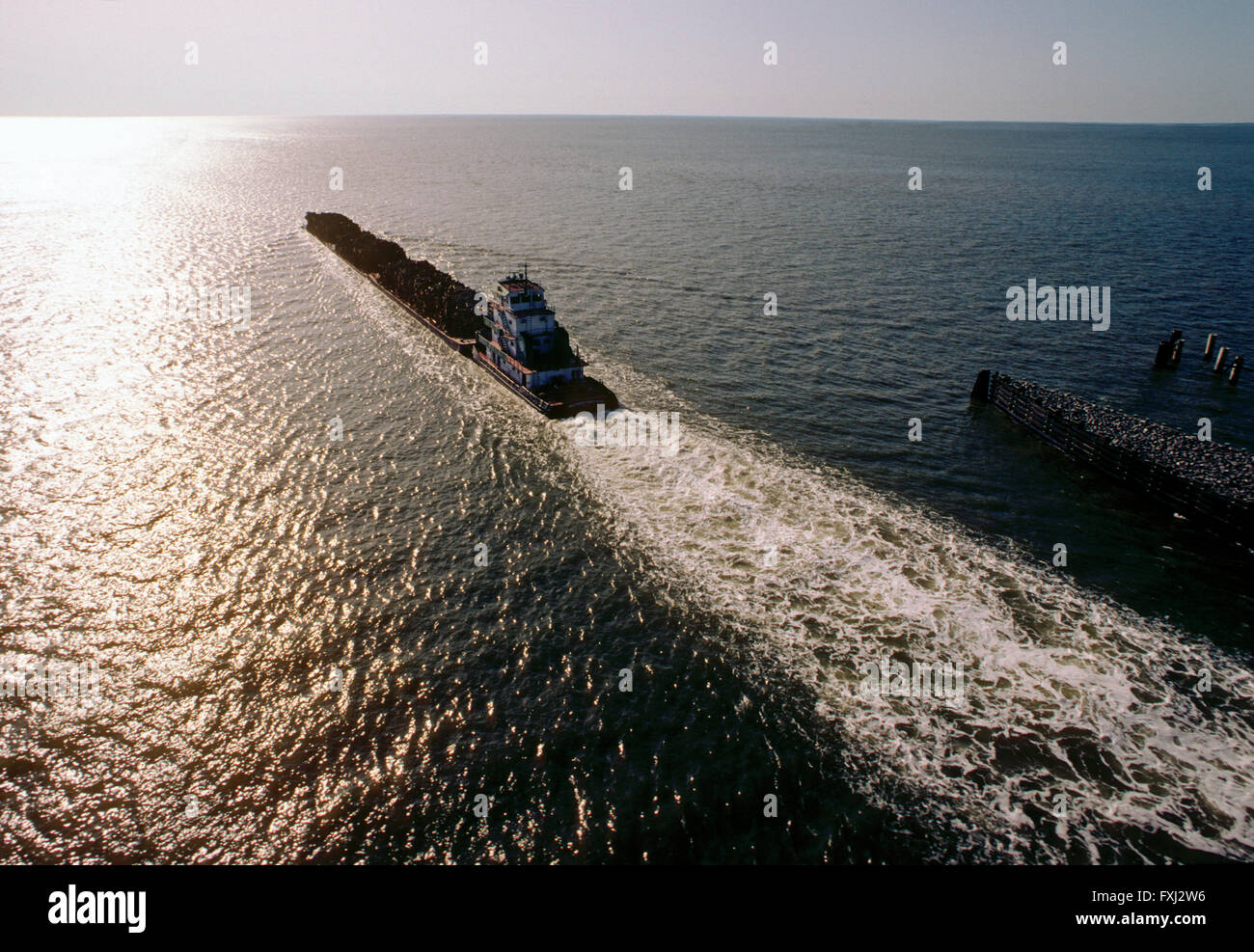 Tug boat pushing barges loaded with logs; Houston Ship Channel; Texas; USA - Stock Image