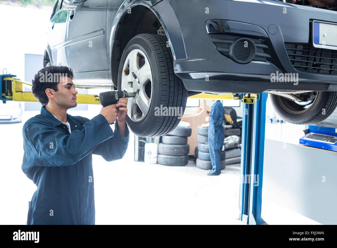 Mechanic fixing a car wheel - Stock Image