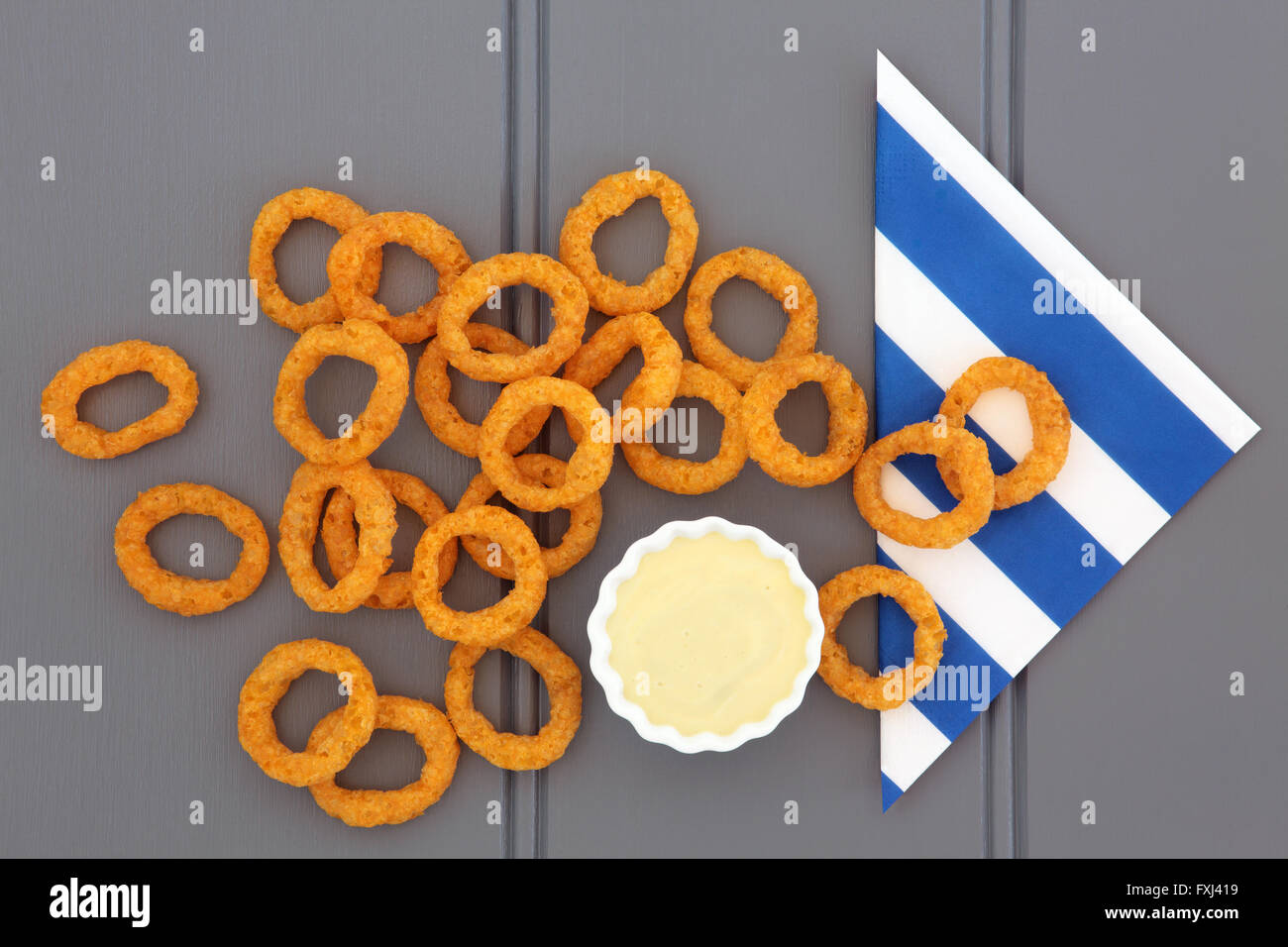 Onion ring snack food with mayo dip and striped napkin. - Stock Image