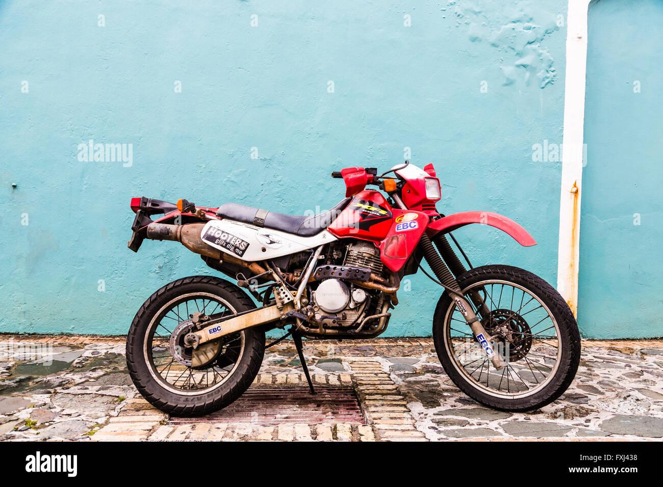 An Old Honda Dirt Bike in Cobblestone Street - Stock Image
