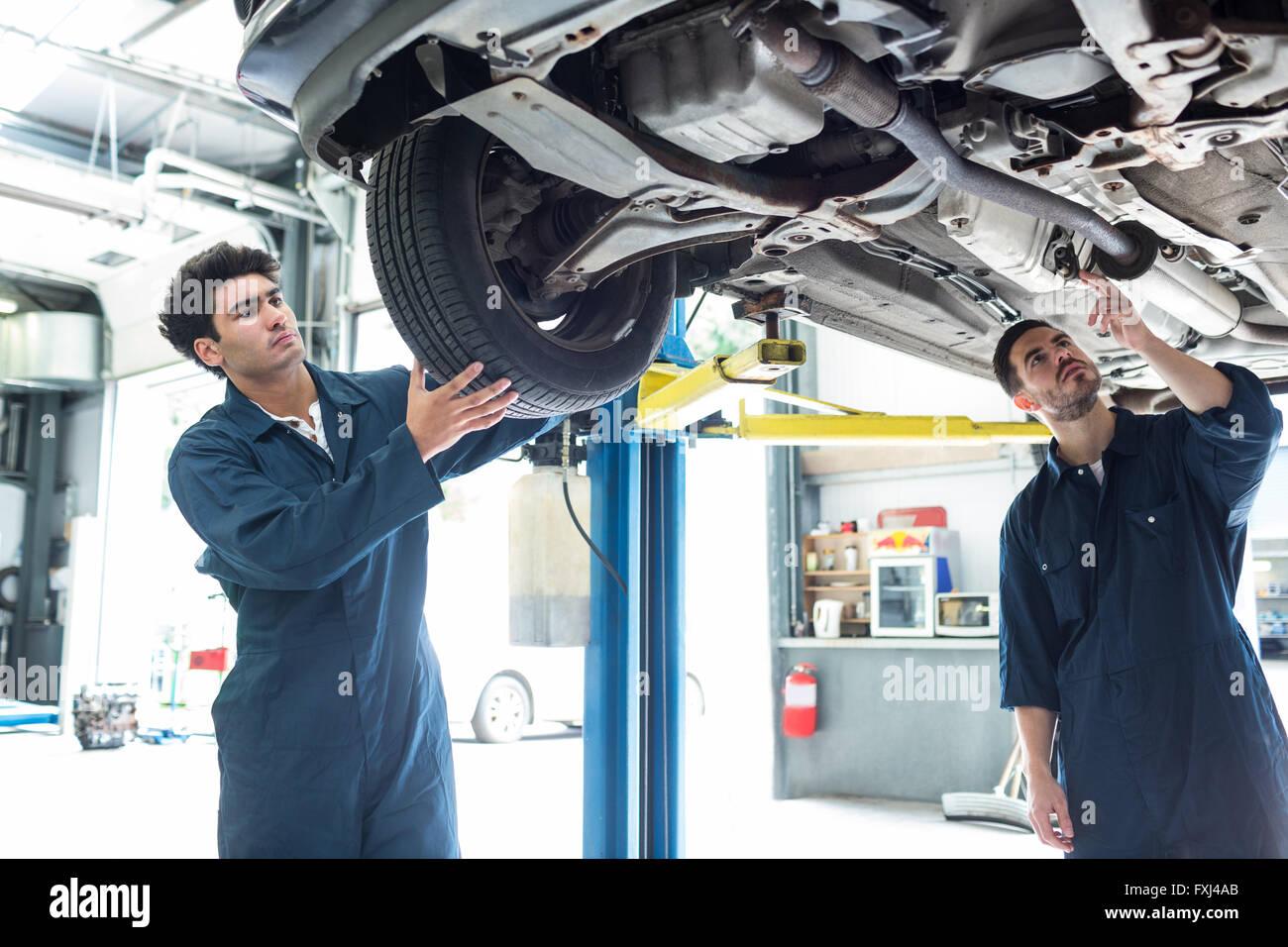 Mechanic fixing a wheel while a colleague examining car - Stock Image