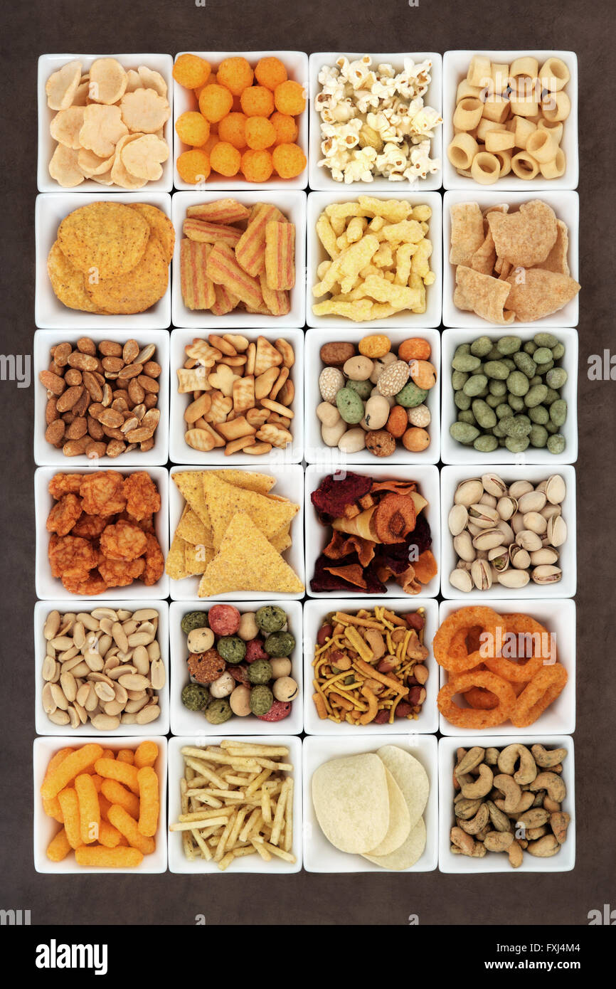 Large savoury snack food selection in square porcelain bowls. - Stock Image