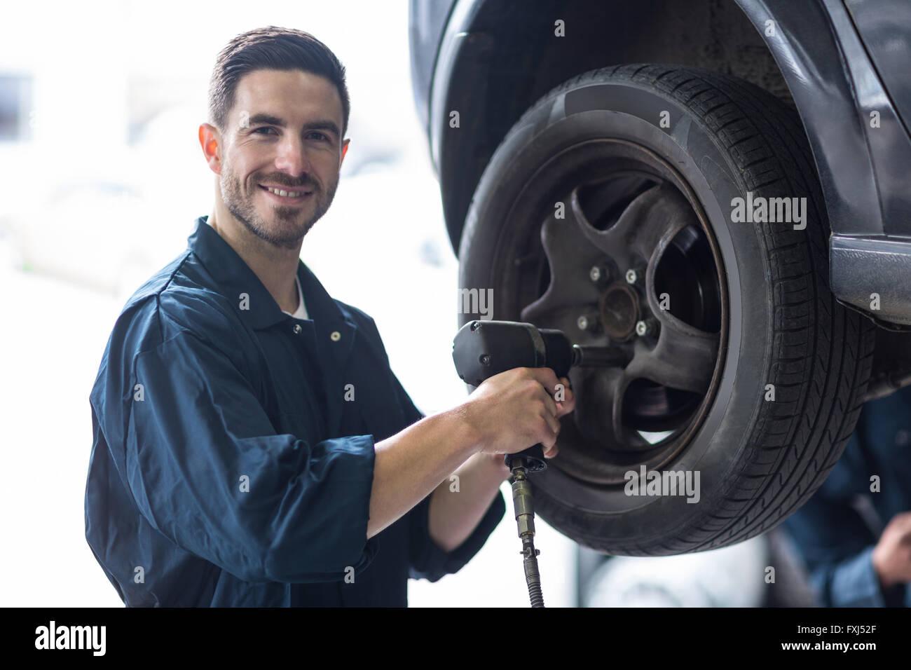 Mechanic fixing a car wheel - Stock Image