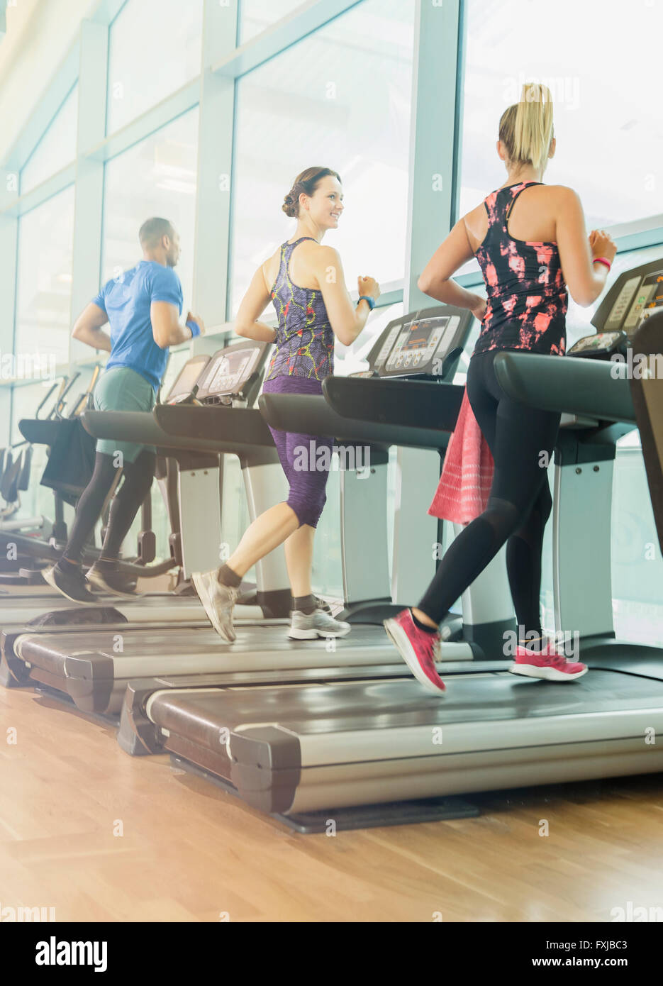 Man and women jogging on treadmills at gym Stock Photo