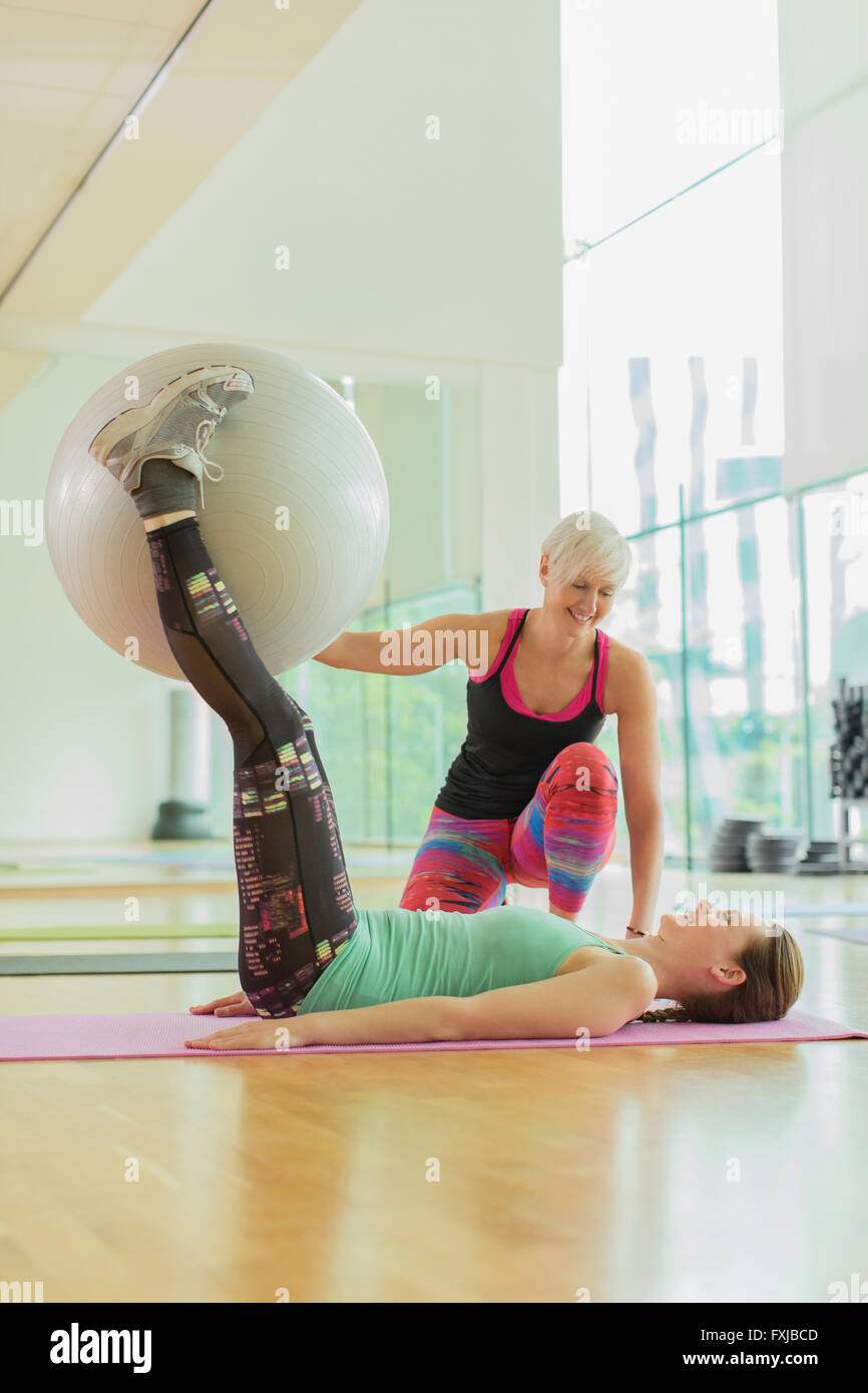 Personal trainer guiding woman with fitness ball between legs - Stock Image