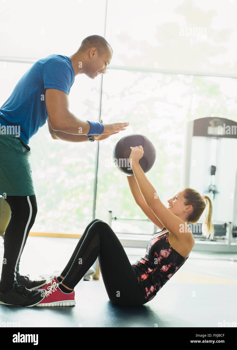 Personal trainer guiding woman with medicine ball at gym Stock Photo