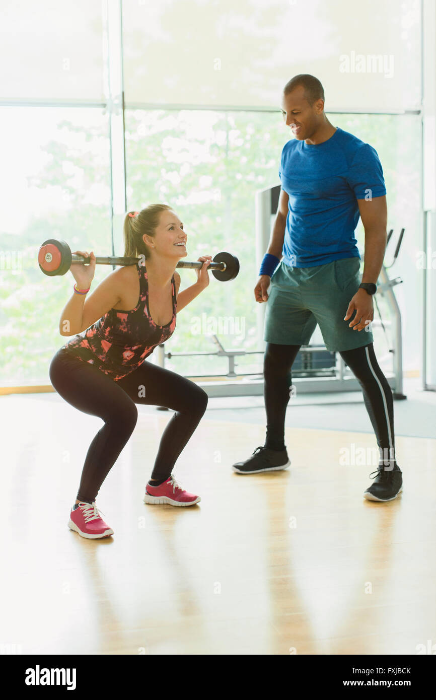Personal trainer guiding woman doing barbell squats at gym - Stock Image