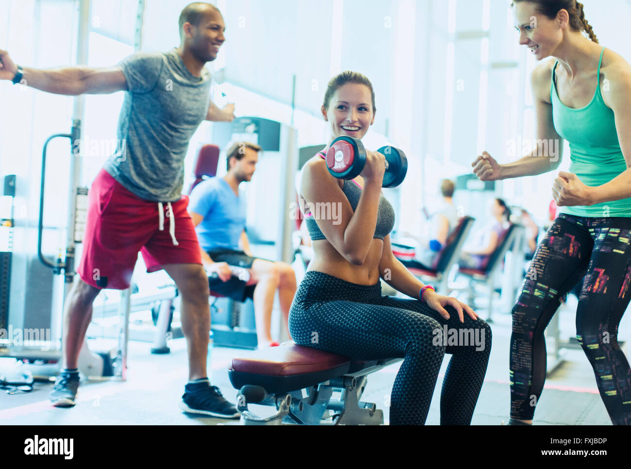 Woman cheering on friend doing dumbbell biceps curls at gym - Stock Image