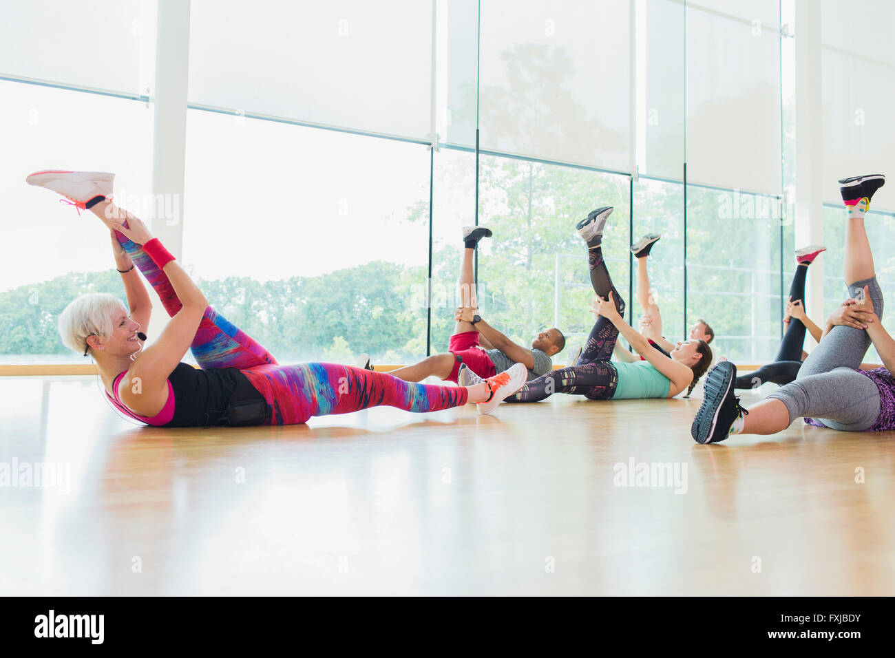 Fitness instructor guiding exercise class stretching legs - Stock Image