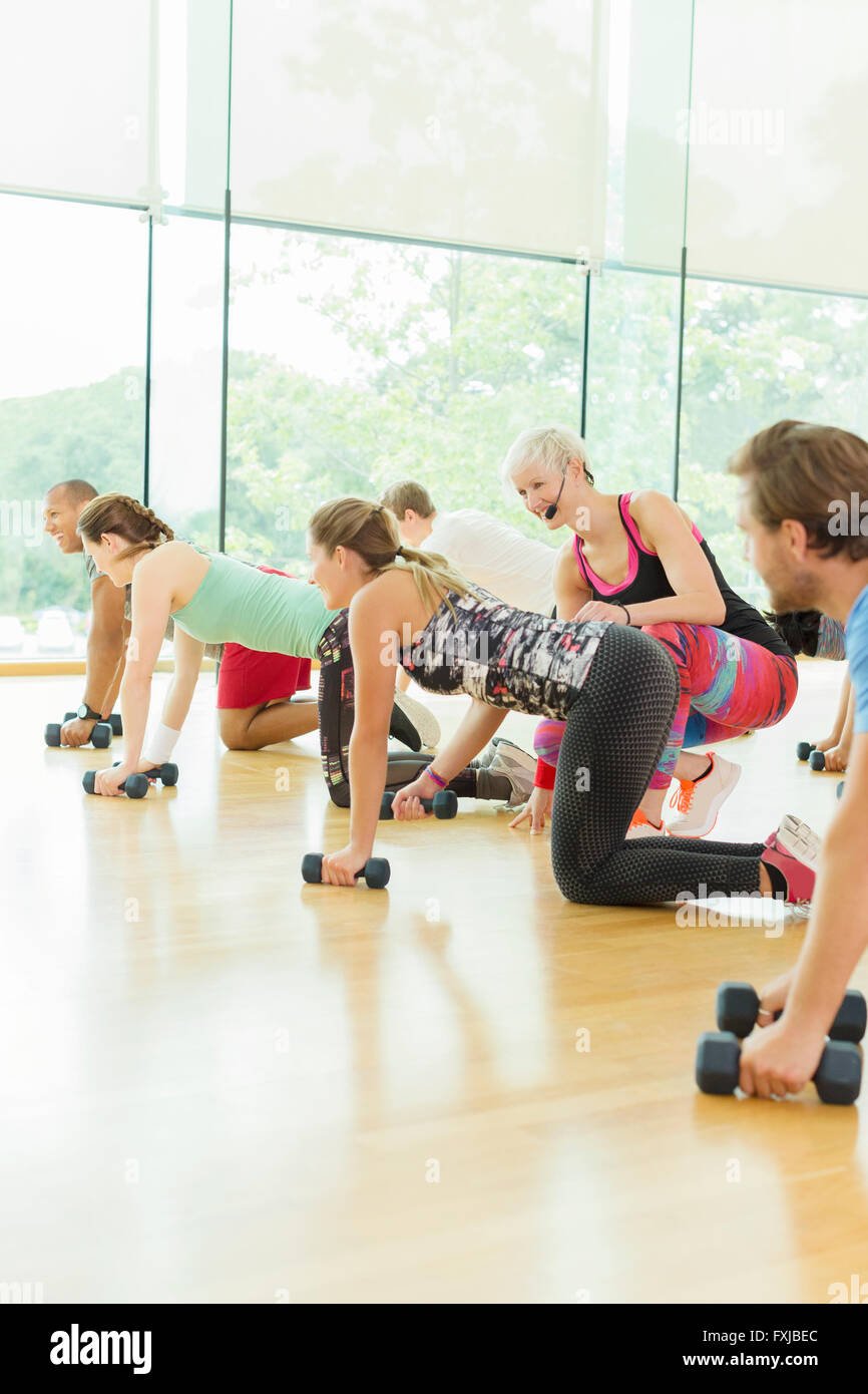 Fitness instructor guiding woman in exercise class - Stock Image