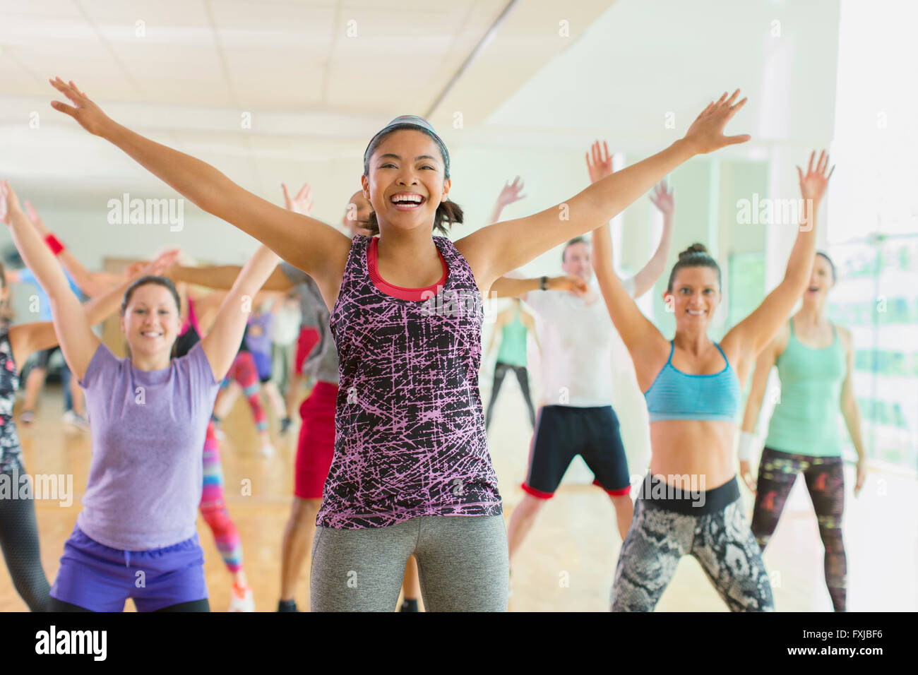 Enthusiastic woman with arms outstretched in aerobics class Stock Photo