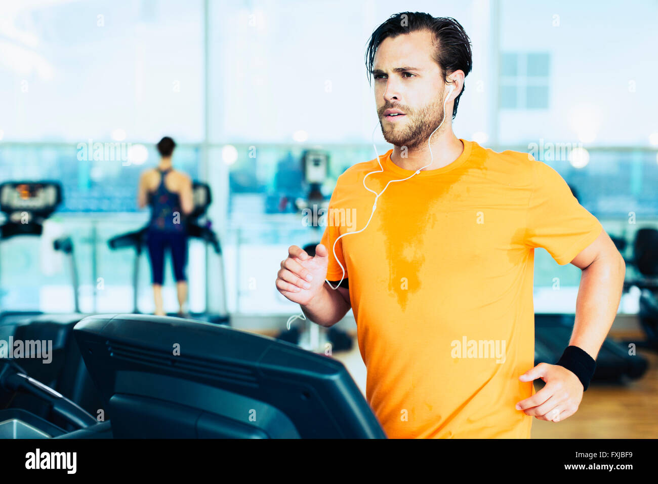 Sweating man with headphones running on treadmill at gym - Stock Image